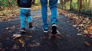 Adult and child feet and legs walking on a road