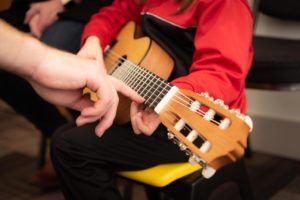 childs hands playing guitar