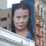 A mural of Greta Thunberg painted on the side of a building.